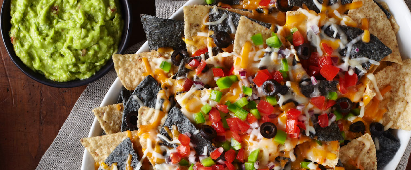 A serving dish of prepared nachos with a variety of toppings surrounded by three bowls containing salsa, sour cream and guacamole
