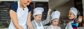 Photo of a group of children having fun while food fighting, during cooking class with a chef