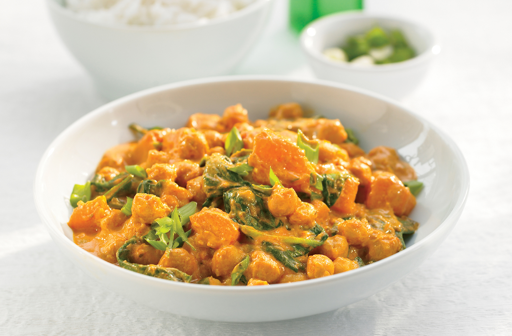 A bowl of curried chick peas & squash korma with spinach & green onions