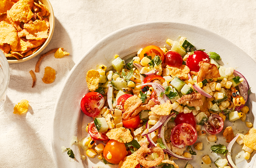 A plate containing a Corn and Tomato Salad with Crispy Corn Flakes on top and in a side dish.