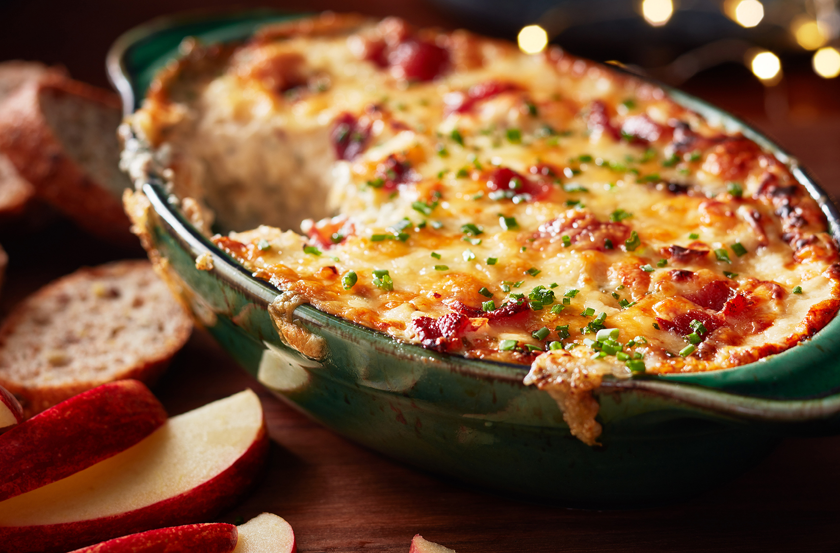 Apple and bread slices wait to be dunked into a cheesy baked dip with bacon