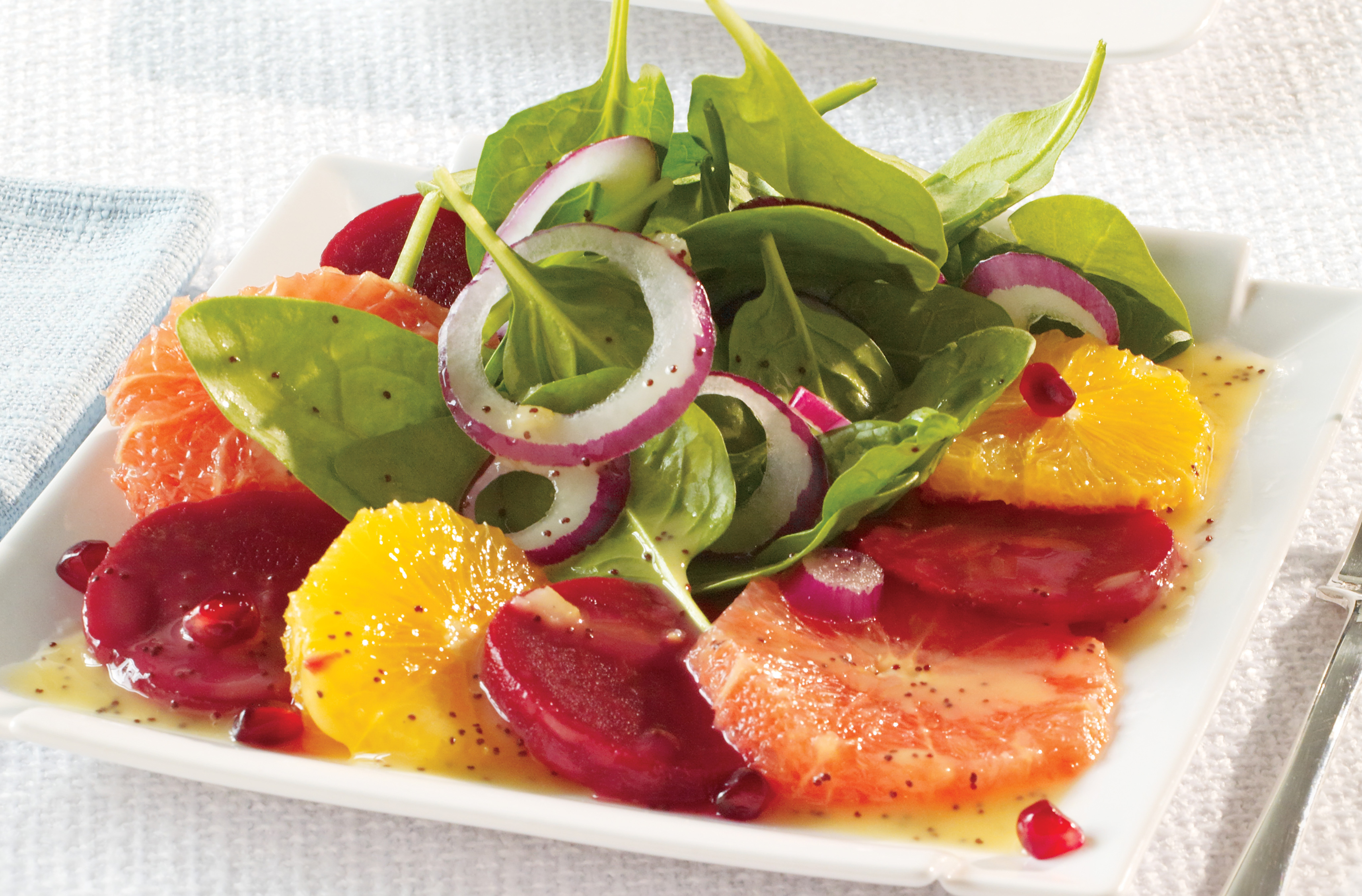 Plate of orange, red grapefruit & beet slices, topped with spinach & onion