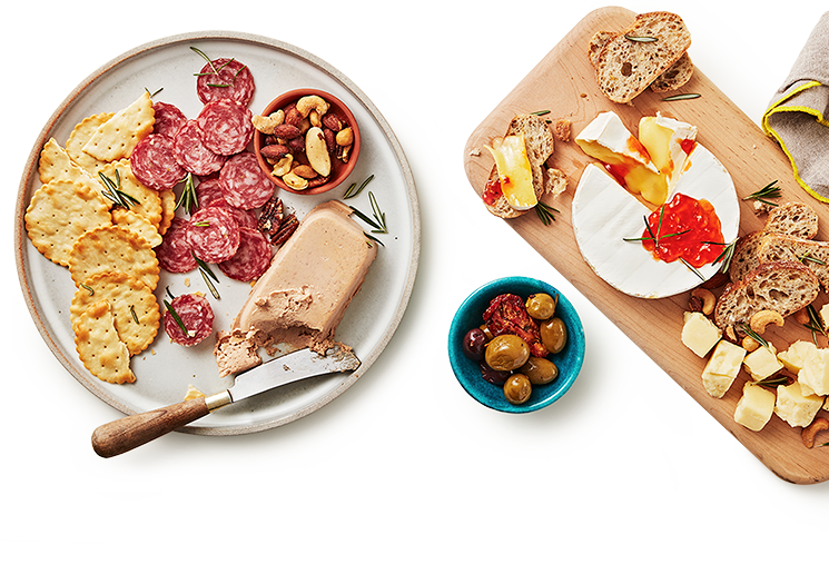 A plate with cheese, crackers and meat slices beside a small bowl of assorted olives and a charcuterie board with baguette slices, a brie with a wedge cut out and chucks of cheese.