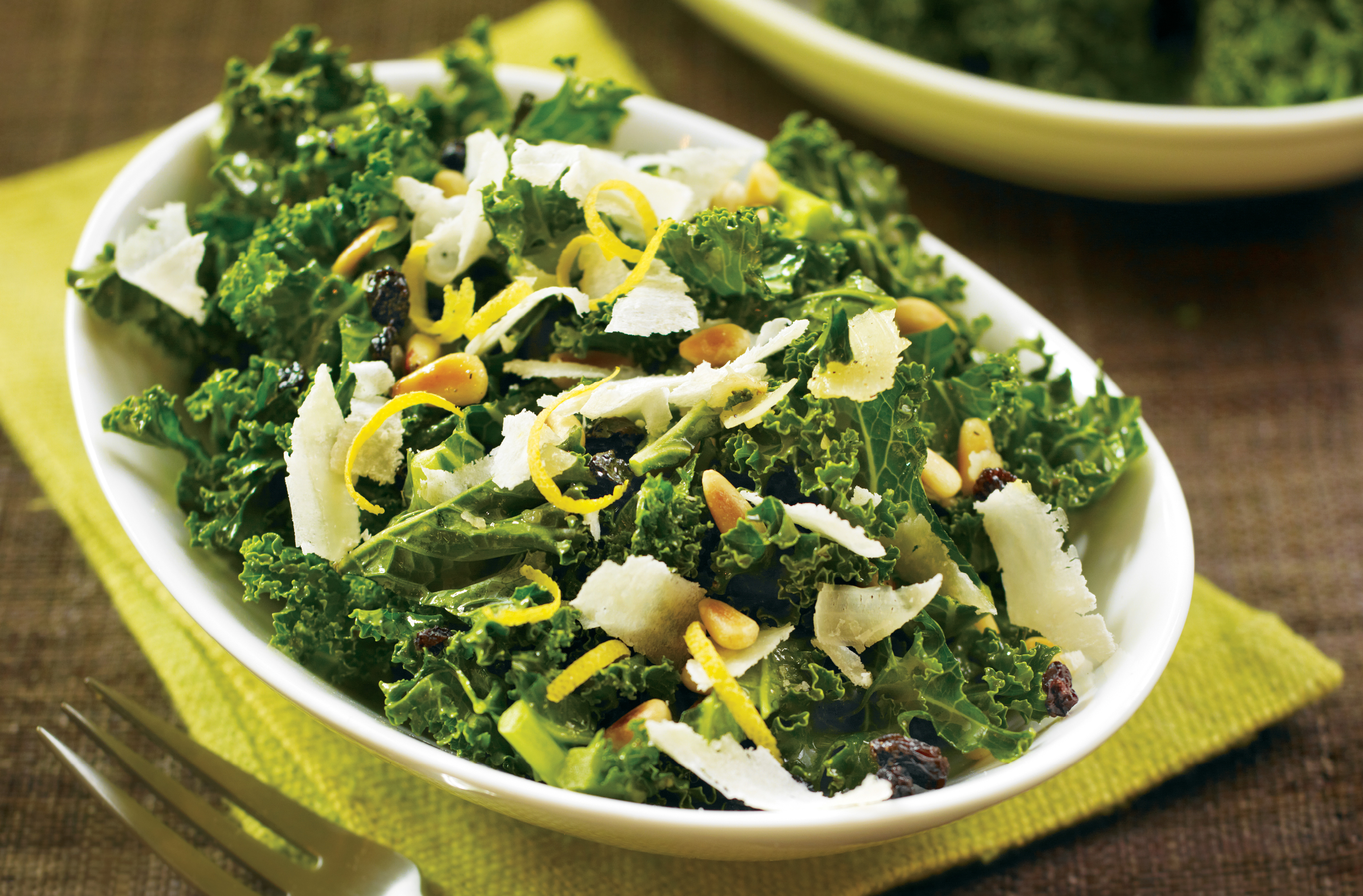 Bowl of kale salad with pine nuts, currants, lemon rind & Pecorino shavings