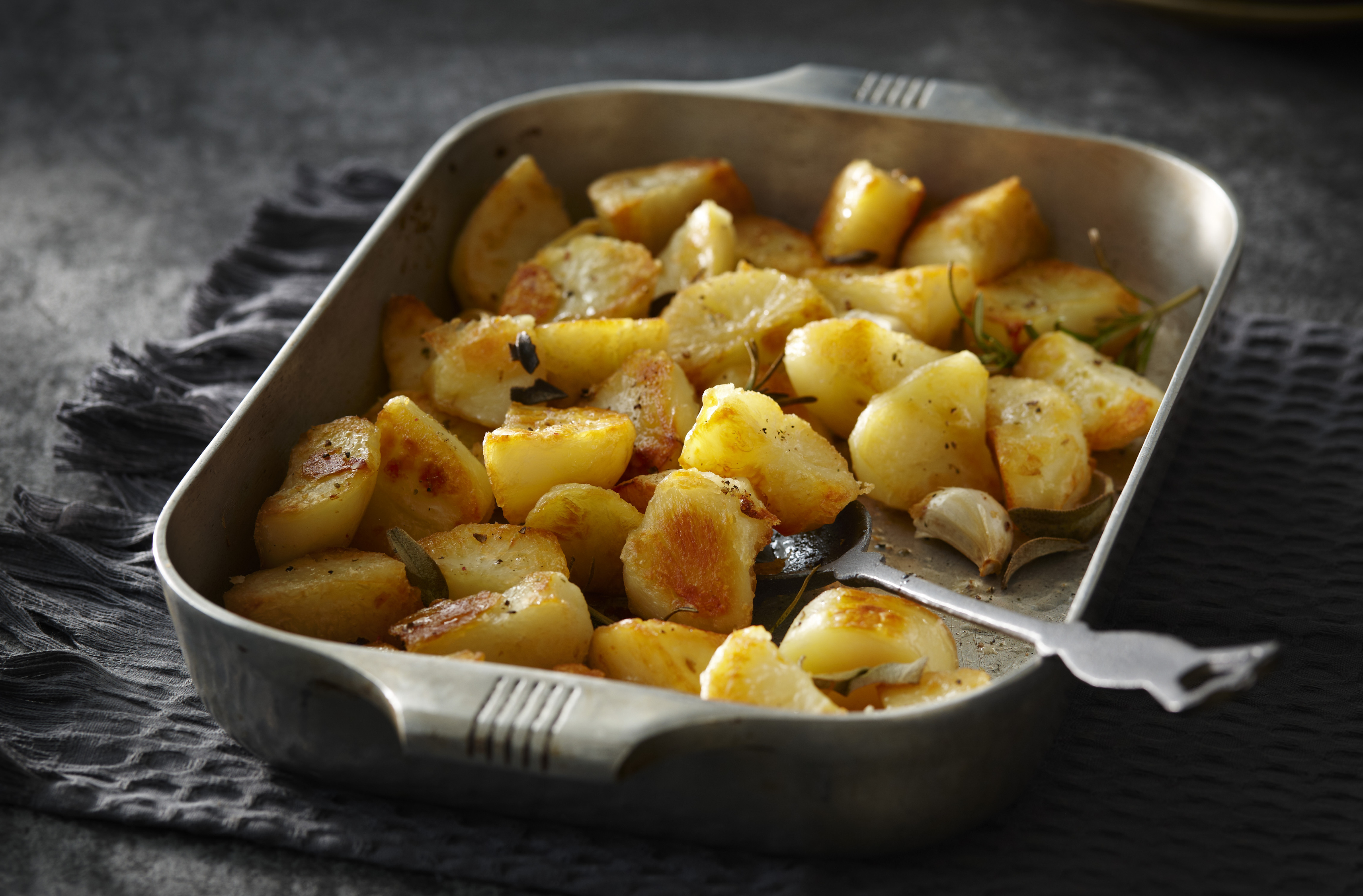 A baking pan of golden potato chunks with herbs, slow-roasted in goose fat