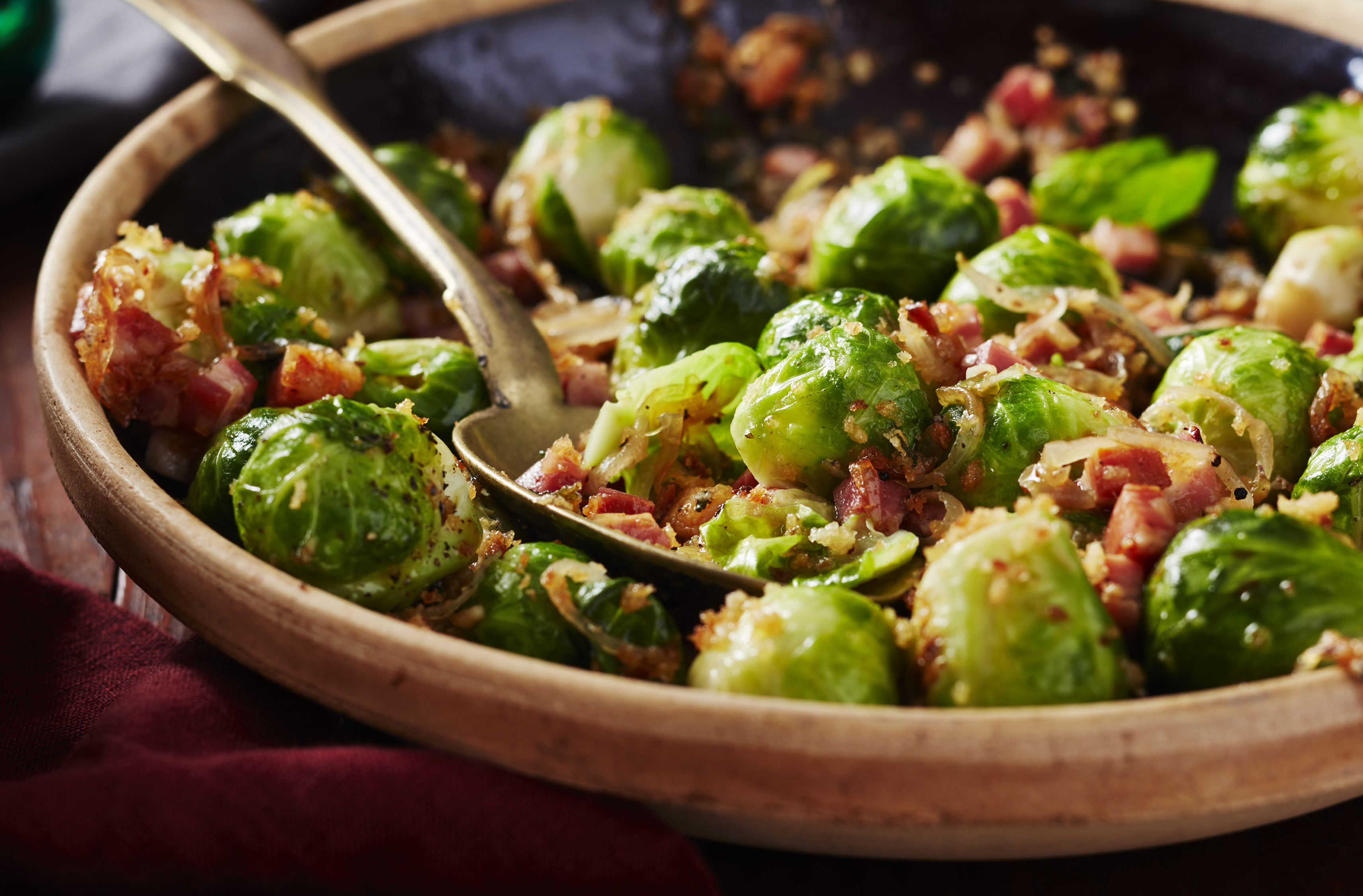 A bowl cradles a spoon and seasoned Brussels sprouts with diced pancetta