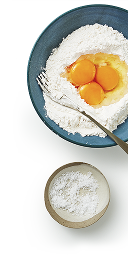 Mixing bowl and fork with a flour mixture and 3 freshly cracked eggs in the middle, beside a small bowl of coconut milk mixture.