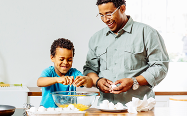 Father and son cracking eggs into a glass bowl in the kitchen