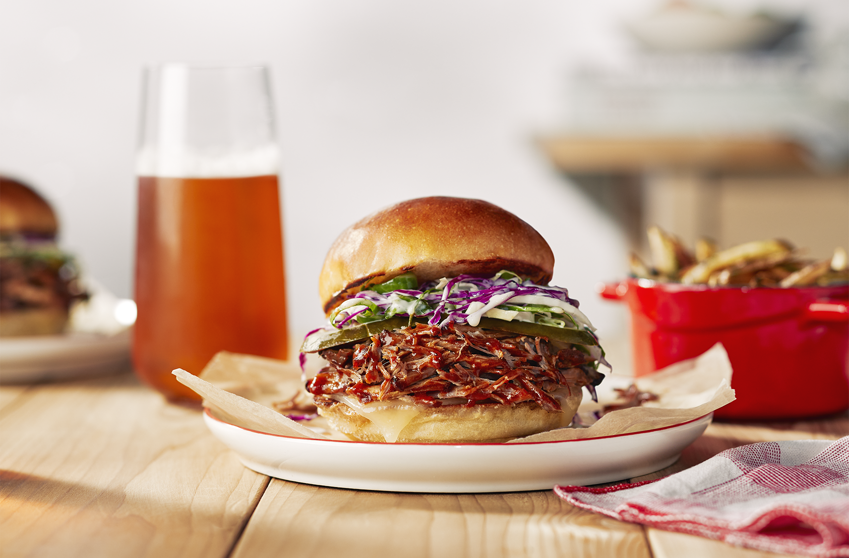 A pulled pork sandwich topped with a creamy slaw on a plate next to a serving of fries and a drink