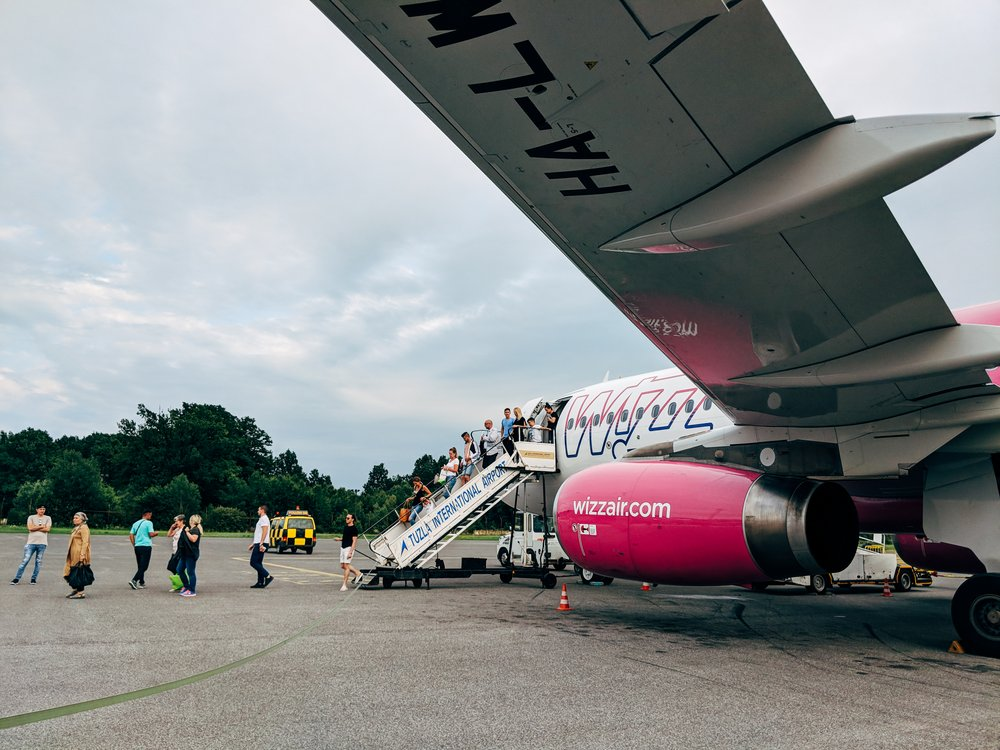 People leaving Wizz Air airplane parked at the airport