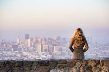 A woman looking into a distance - Easy ways to save money on travel