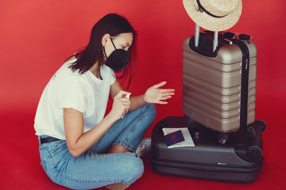 Young woman with suitcase using hand sanitizer