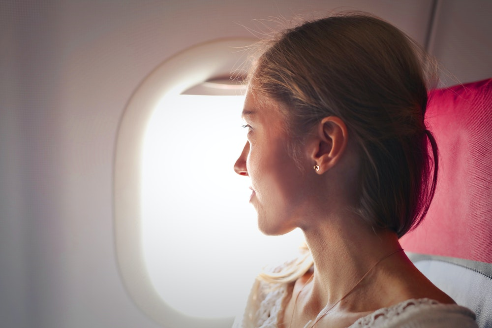Woman sitting next to the window on an airplane