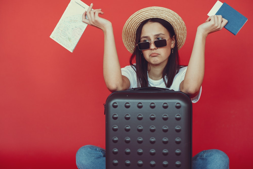 Young disappointed woman sitting next to a suitcase