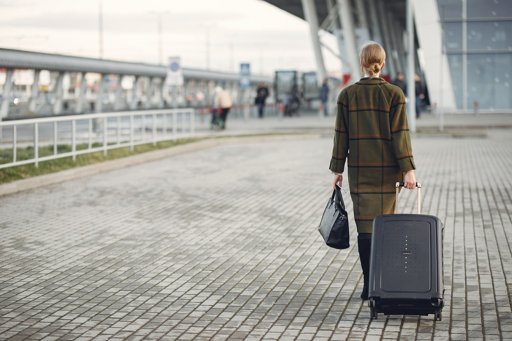 Woman with a suitcase walking to the airport