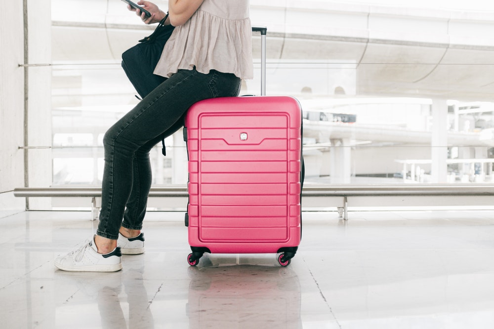 Woman sitting on a pink suitcase