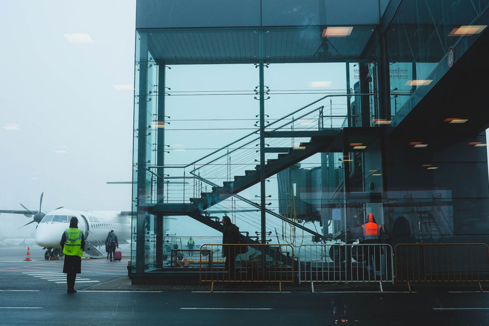 Plane at the airport and person walking next to it