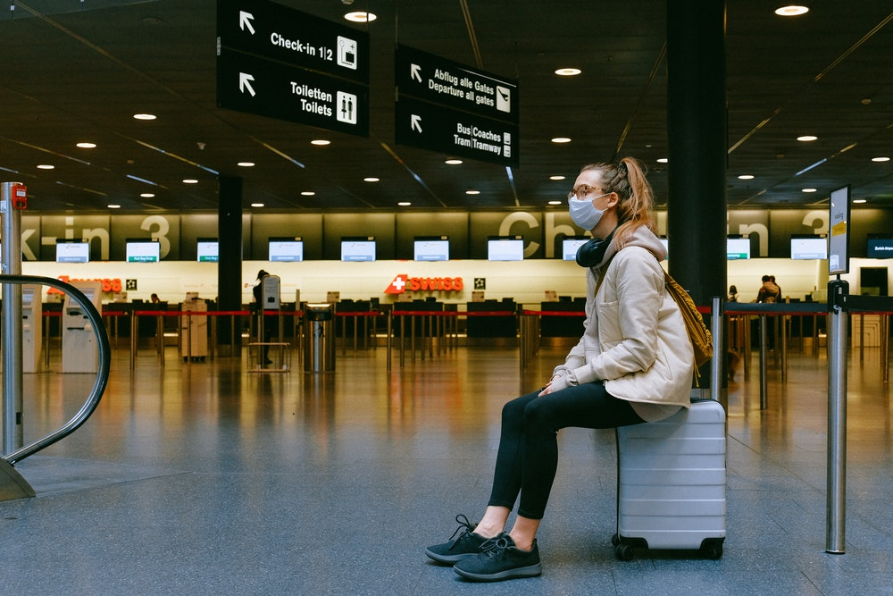 Woman wearing a face mask sitting on a suitcase