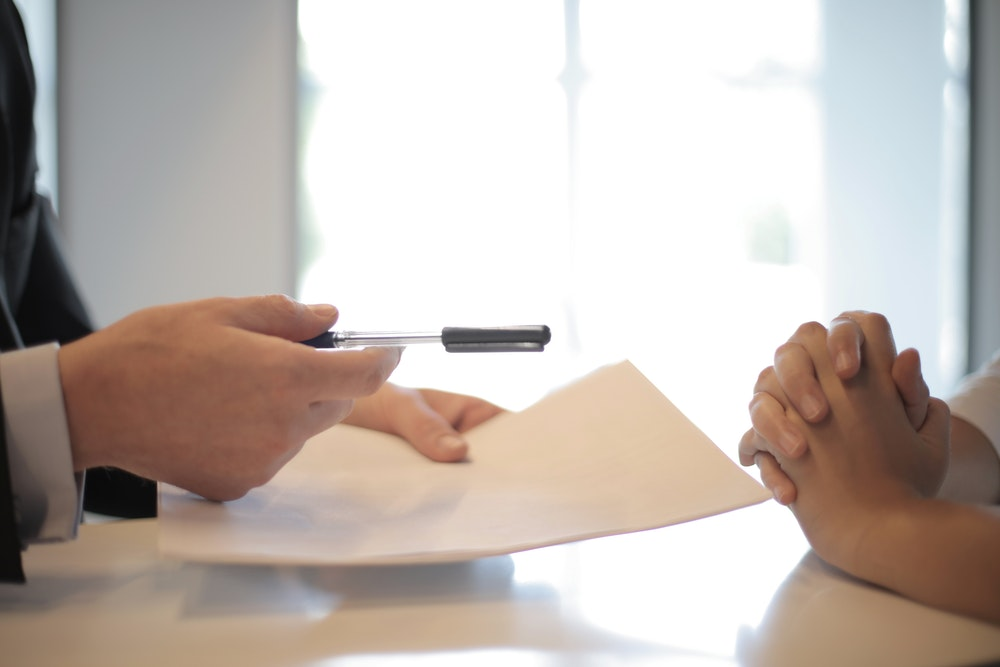 Handing over a paper and a pen