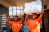 Women holding bales of insecticide-treated bednets provided by the Against Malaria Foundation.