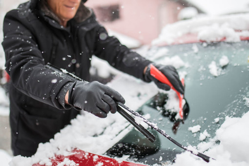 Old man scraping snow off car window