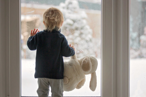 Toddler looking out window at snow