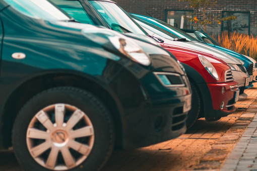 A row of cars parked outside an apartment block