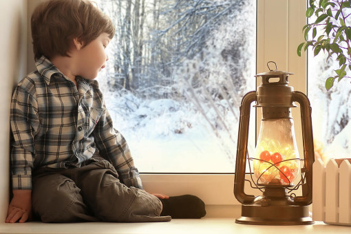 Young boy looking out the window at snow