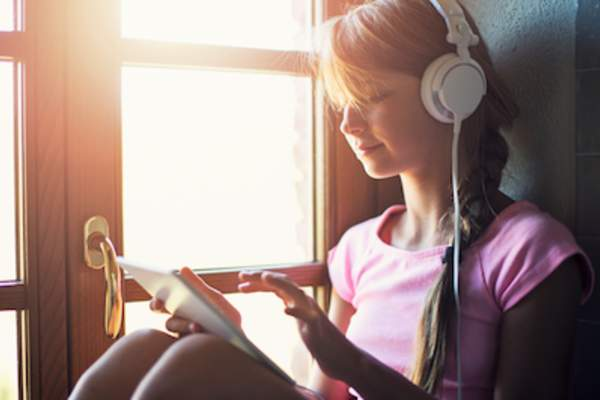 Teen listening to music on tablet