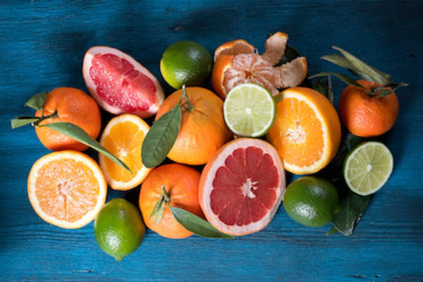 Citrus fruits on blue wood table.