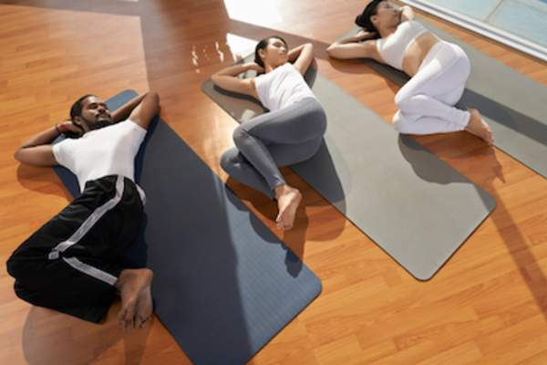 Three people doing spinal twist in yoga class.