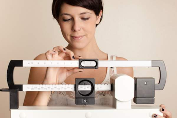 Woman weighing herself on gym scale.