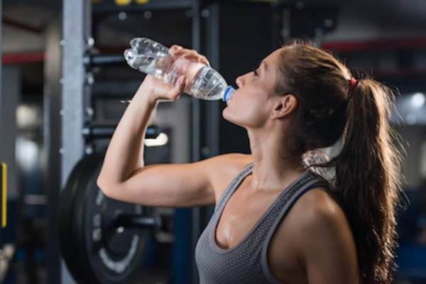 Woman drinking water at gym.