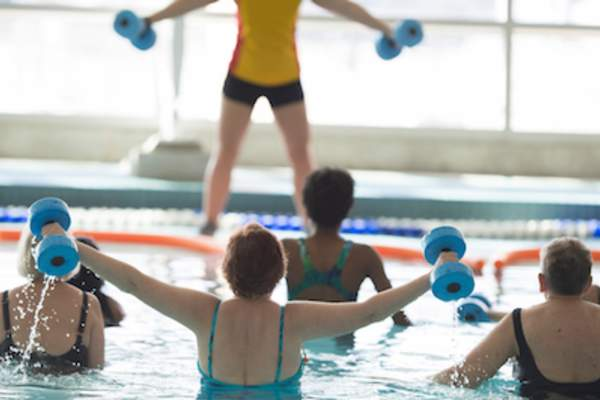Woman working out in pool aerobics class.
