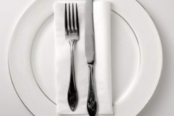 Table setting with plate, napkin, knife, and fork.