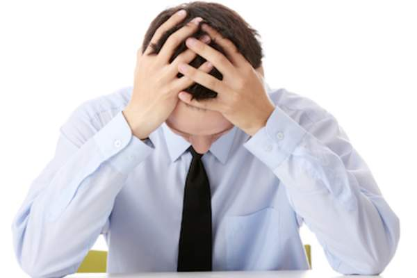 Man with head down and hands on head, work stress.