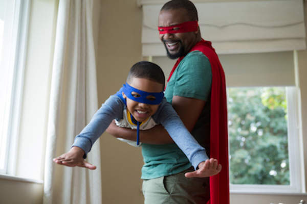 Father playing super heros with kid.