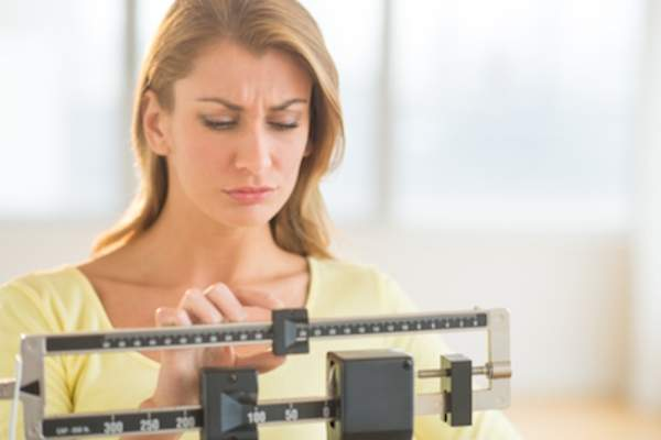 Woman weighing herself, concerned about weight gain.