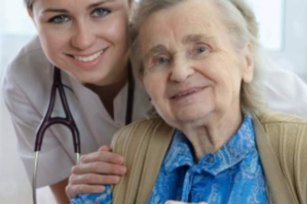 Smiling nurse and senior woman with cane.