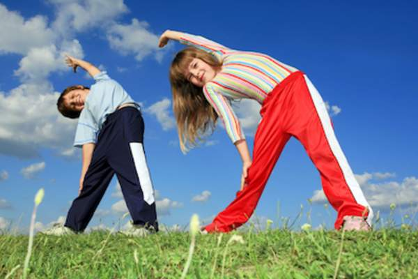 two young children exercising in field