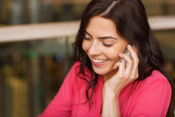 Smiling woman on cell phone.