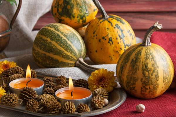 Pumpkin scented candle centerpiece in front of pumpkins.