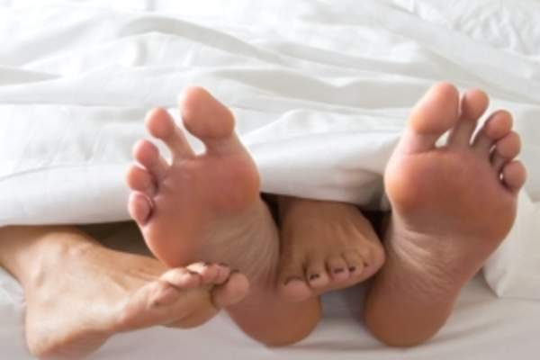 The feet of a couple sticking out from under the sheets