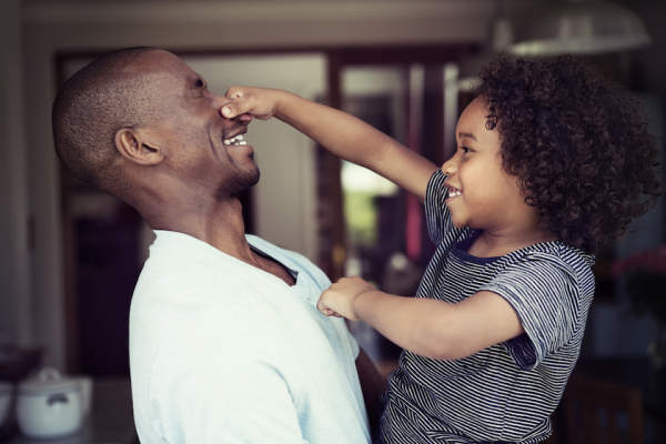 Boy grabbing his father's nose.