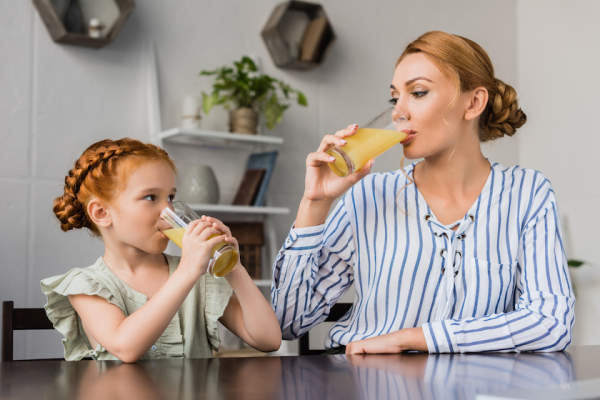 Mother and daughter drinking orange juice.