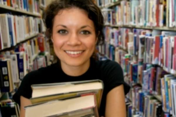 Young woman holding books in library.