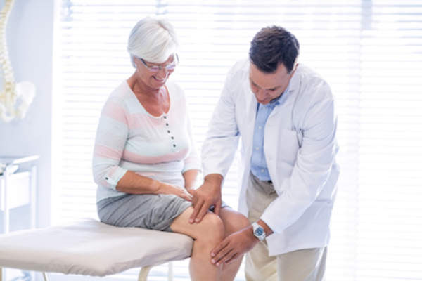 Doctor examines woman's knee for osteoarthritis