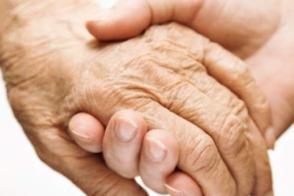 Elderly hand holding a younger one.