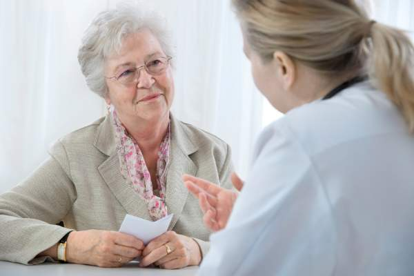 Senior woman getting a prescription from her doctor.