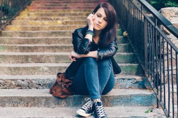 Depressed young woman sitting on stairs.